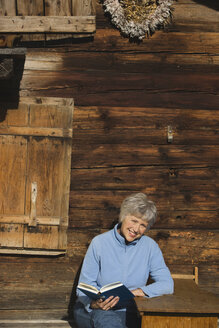 Austria, Senior woman reading book by log cabin - WESTF10490