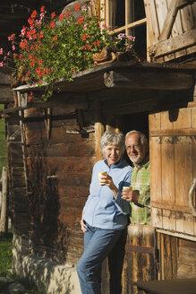 Austria, Karwendel, Senior couple leaning on log cabin, holding mugs - WESTF10469