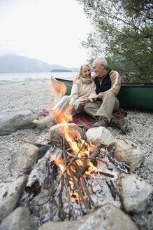 Germany, Bavaria, Senior couple sitting at campfire - WESTF10223