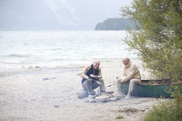 Germany, Bavaria, Senior couple sitting at campfire, grilling fish - WESTF10220