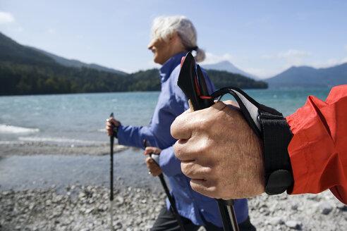 Germany, Bavaria, Walchensee, Senior couple, Nordic Walking on lakeshore - WESTF10180