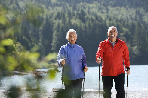 Germany, Bavaria, Walchensee, Senior couple, Nordic Walking on lakeshore - WESTF10174