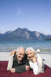Germany, Bavaria, Walchensee, Senior couple relaxing on lakeshore - WESTF10147