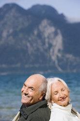 Germany, Bavaria, Senior couple relaxing on lakeshore, sitting back to back, smiling, portrait - WESTF10144
