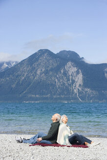 Germany, Bavaria, Senior couple relaxing on lakeshore, sitting back to back - WESTF10141