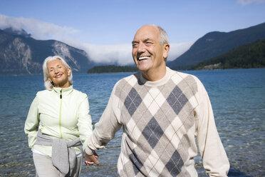 Germany, Bavaria, Walchensee, Senior couple walking hand in hand - WESTF10128