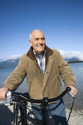 Germany, Bavaria, Walchensee, Senior man pushing bike, smiling - WESTF10110