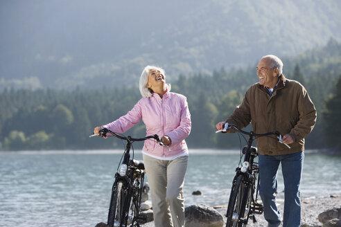 Germany, Bavaria, Walchensee, Senior couple pushing bikes across lakeshore - WESTF10107