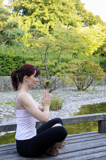 Germany, Bavaria, Munich, Young woman exercising yoga, hands folded - NHF00973