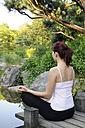 Germany, Bavaria, Munich, Young woman exercising yoga, rear view - NHF00970