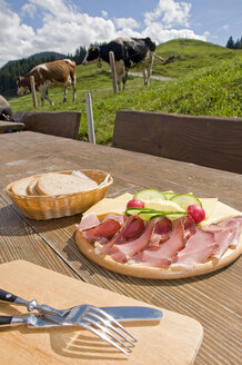 Germany, Allgäu, Törggelen, Solid snack on table, cattle in background - GNF01073