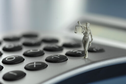 Justitia figurine on calculator, close up - ASF03840