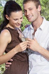 Young couple flirting, holding wine glasses, close-up - ABF00483