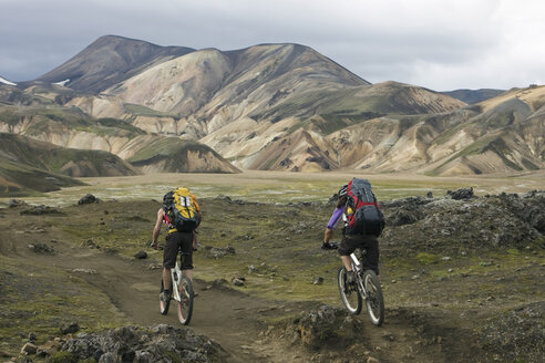 Iceland, Men mountain biking in hilly landscape - FF00993