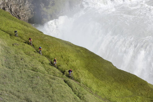 Iceland, Men mountain biking next to waterfall - FF00984