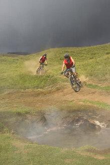 Iceland, Men mountain biking in hilly landscape - FF00981