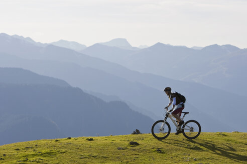 Austria, Salzburger Land, Zell am See, Woman mountain biking - FFF01027