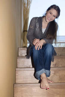 Young woman sitting on stairs, smiling, portrait - NHF01056