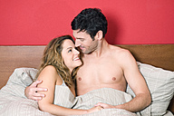 Young couple in bed, smiling, portrait - NHF00984