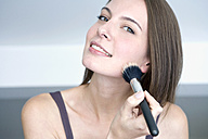 Young woman using make-up brush, portrait, close up - WESTF10911