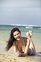 Young woman lying on beach, smiling, portrait - ABF00514