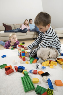 Family relaxing at home, children playing with building bricks - CLF00676