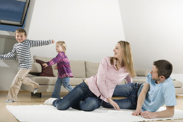 Family relaxing at home, children frolicking - CLF00670