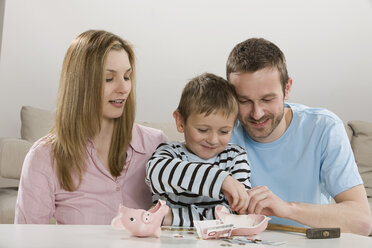 Parents and son (4-5) looking at broken piggybank, counting money - CLF00628