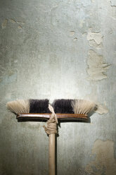 Broom leaning against wall, close-up - JR00069