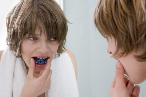 Germany, boy (12-13) putting in braces looking into mirror - WDF00431