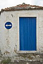 Greece, Ithaca, Old house with blue door, road sign on wall - MU00805