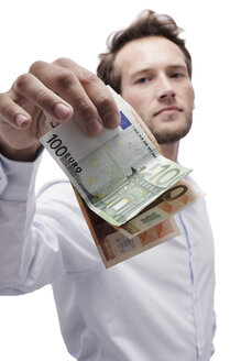 Young man holding Euro notes, portrait - BMF00567