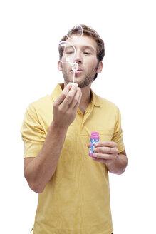 Young man blowing soap bubbles, portrait - BMF00537