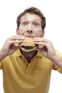 Young man eating Hamburger, portrait, close-up - BMF00531