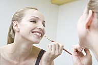 Young woman applying lipstick, smiling, portrait - WESTF10815
