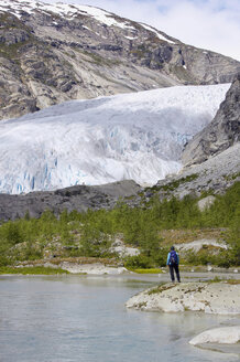 Norway, Nigardsbreen, Glacier tongue, Hiker on shore, rear view - MR01168