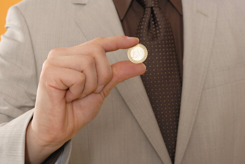 Man holding Euro coin, middle section, close up - KJF00029