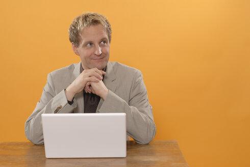 Man sitting at laptop, smiling, portrait - KJF00020