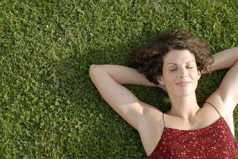 Young woman lying on lawn, eyes closed, smiling, elevated view, portrait - KJF00061