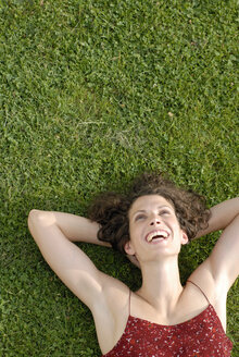 Young woman lying in meadow, laughing, elevated view, portrait - KJF00055