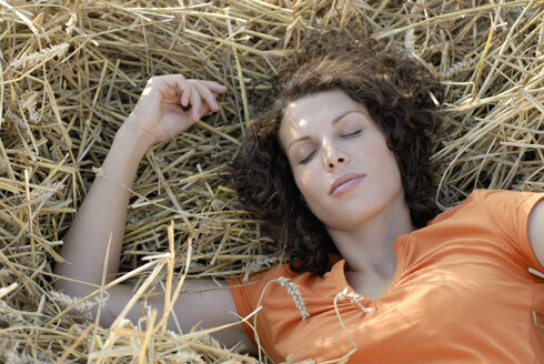 Young woman sleeping in hay, eyes closed, portrait - KJF00046