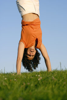 Young woman doing handstand on meadow - KJF00043