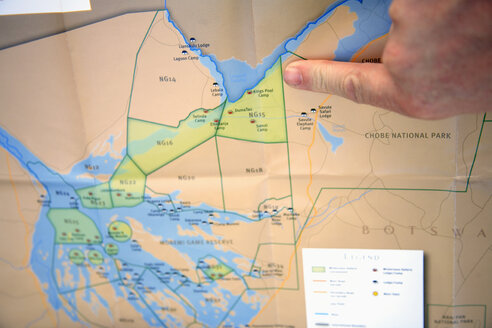 Africa, Botswana, Okavango Delta, Person pointing on map - PK00343