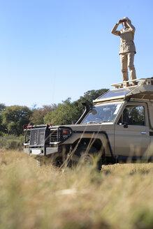 Africa, Botswana, Okavango Delta, Man on safari using binoculars - PK00325