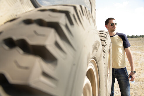 Africa, Botswana, Okavango Delta, Man standing next large wheel - PK00322