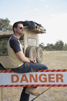Africa, Botswana, Okavango Delta, Man sitting on danger sign - PK00319