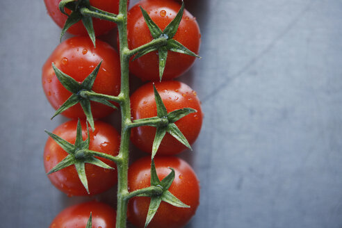 Bunch tomatoes on metal plate, elevated view, close-up - KSWF00438