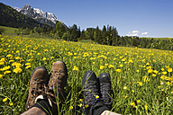 Austria, Tyrol, Kaisergebirge, Hikers relaxing on meadow, close-up - GWF00980