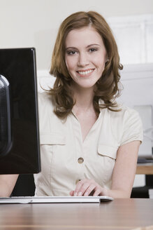 Germany, Munich, young woman working in office, smiling, portrait - LDF00648