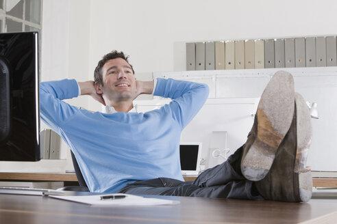 Germany, Munich, businessman in office , feet on desk - LDF00639